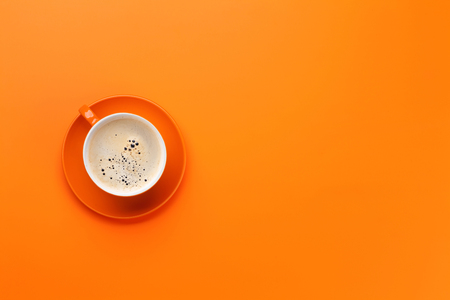 Orange coffee cup over orange background. Top view flat lay with copy space