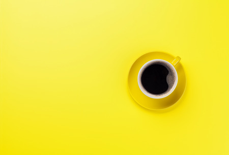 Yellow coffee cup over yellow background. Top view flat lay with copy space