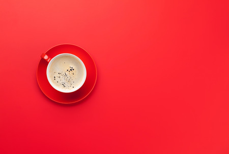 Red coffee cup over red background. Top view flat lay with copy space