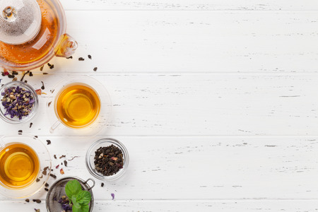 Different herbal and fruit dry teas, teapot and cups on wooden table. Top view flat lay with copy space