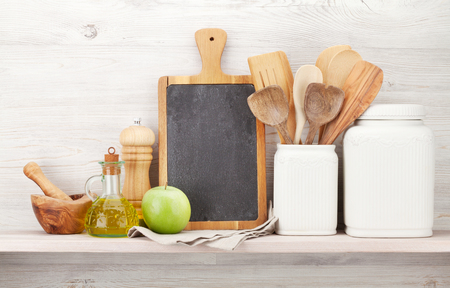 Set of various kitchen utensils. In front of wooden wall with chalkboard for your text