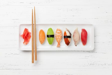 Japanese sushi set. Sashimi, maki rolls. On plate over white wooden background with space for your text