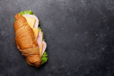 Croissant sandwich on stone table. French breakfast. Top view flat lay with copy space for your text
