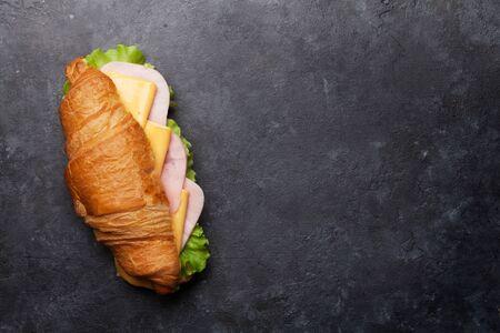 Sándwich de croissant en mesa de piedra. Desayuno francés. Vista superior plana con espacio de copia para su texto