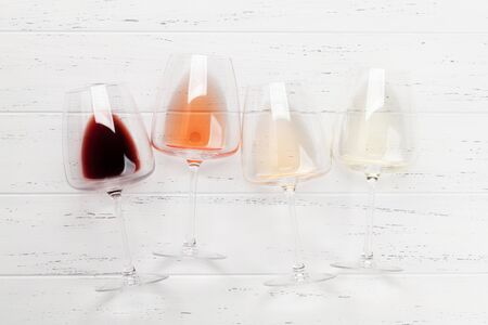 Various wine glasses on wooden table. Red, rose and white wines. Top view flat lay with copy space for your text