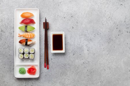 Japanese sushi set. Sashimi, maki rolls. On plate over stone background with space for your text Stock Photo