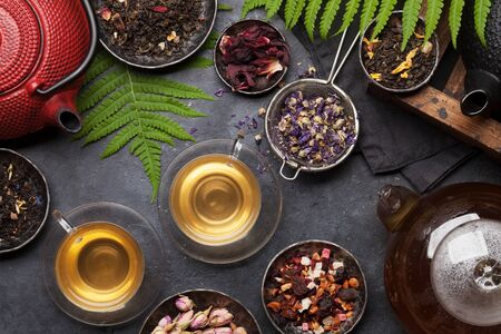Set of different herbal and fruit dry teas on stone table. Top view flat lay 版權商用圖片