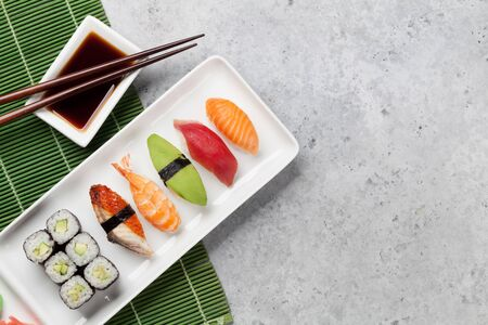 Japanese sushi set. Sashimi, maki rolls. On plate over stone background with space for your text 版權商用圖片