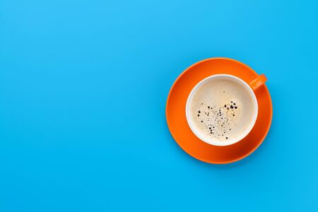 Orange coffee cup over blue background. Top view flat lay with copy space