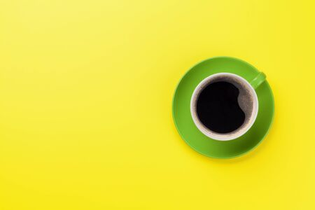 Green coffee cup over yellow background. Top view flat lay with copy space