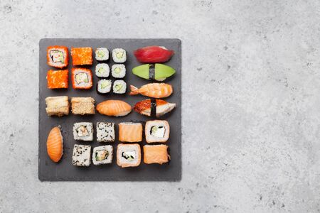 Japanese sushi set. Sashimi, maki rolls. On plate over stone background. Top view flat lay with copy space for your text