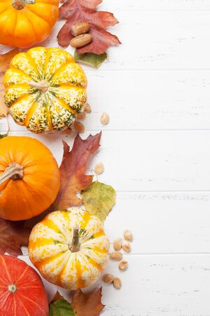 Autumn backdrop with pumpkins and colorful leaves over wooden background. Top view with space for your text Stock Photo