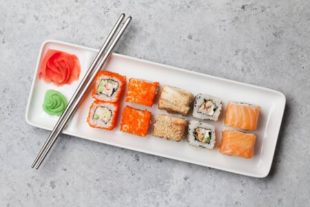 Japanese sushi set. Sashimi, maki rolls. On plate over stone background