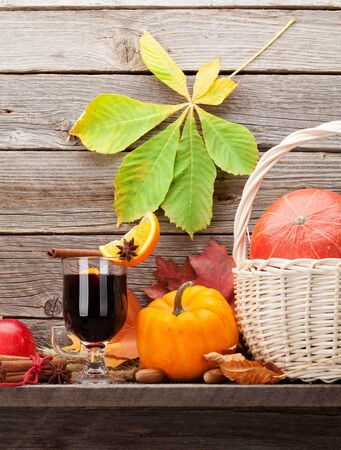 Autumn still life with mulled wine, pumpkins, apples, pears and colorful leaves in front of wooden wall Stock Photo