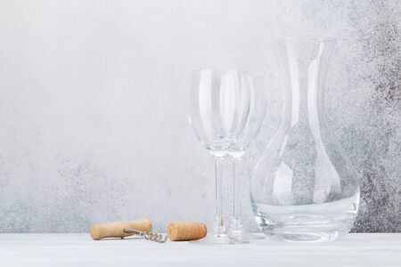 Wine glasses and decanter on wooden table. In front of stone wall with space for your text 스톡 콘텐츠