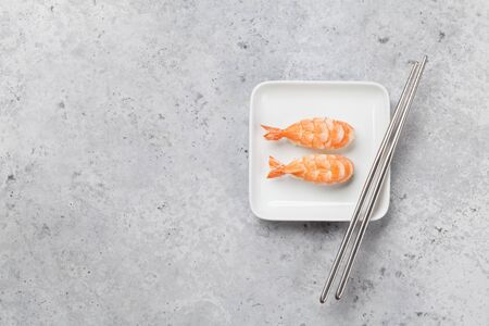 Japanese sushi set with shrimps. Ebi. Sashimi, maki rolls. On plate over stone background with space for your text
