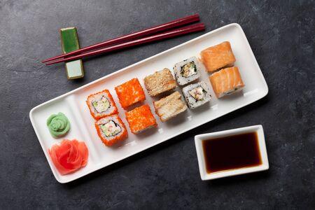 Japanese sushi set. Sashimi, maki rolls. On plate over dark stone background