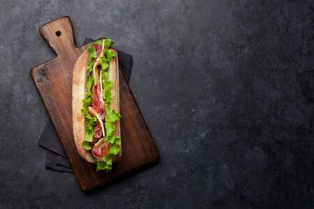Fresh submarine sandwich with prosciutto ham, cheese and lettuce on dark stone background. Top view with copy space for your text Reklamní fotografie