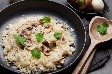 Delicious mushrooms risotto dressed with parmesan cheese and parsley
