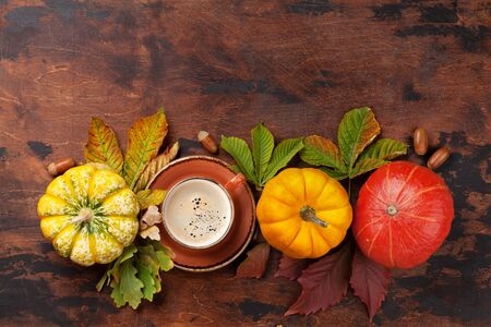 Autumn still life with pumpkins, coffee and colorful leaves over wooden background. Top view with space for your text Stock Photo