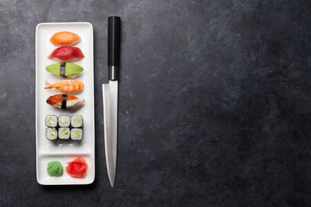 Japanese sushi set. Sashimi, maki rolls. On plate over dark stone background with space for your text Stok Fotoğraf