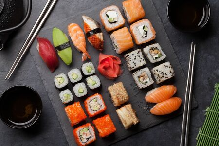Set de sushi japonés. Sashimi, maki rolls y té verde. Sobre tablero de pizarra sobre fondo de piedra oscura
