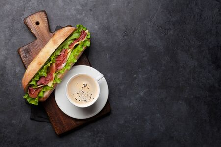 Fresh submarine sandwich with prosciutto ham, cheese and lettuce with coffee cup on stone background. Top view with copy space for your text Stock fotó