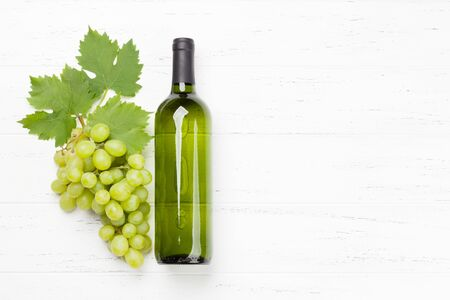 White wine bottle and grape on wooden table. Top view flat lay with copy space for your text