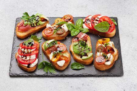 Tapas tradicionales españolas con tomate, queso mozzarella, aguacate y jamón serrano sobre tablero de piedra