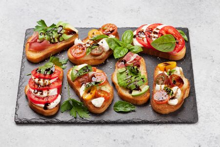 Traditional spanish tapas with tomatoes, mozzarella cheese, avocado and prosciutto on stone board