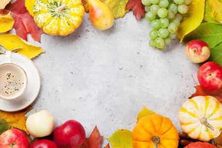 Autumn backdrop with pumpkins, apples, pears, grapes and colorful leaves over stone background. Top view with space for your text Stock Photo