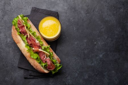 Świeża kanapka podwodna z szynką prosciutto, serem i sałatą na ciemnym tle kamienia. Widok z góry z miejscem na kopię tekstu Zdjęcie Seryjne
