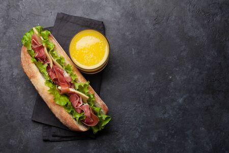 Sándwich submarino fresco con jamón prosciutto, queso y lechuga sobre fondo de piedra oscura. Vista superior con espacio de copia para su texto. Foto de archivo
