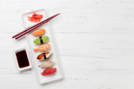Japanese sushi set. Sashimi, maki rolls. On plate over wooden background. Top view flat lay with copy space for your text