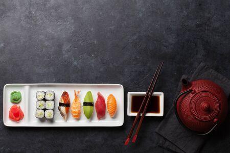 Insieme di sushi giapponese. Sashimi, involtini di maki e tè verde. Sulla piastra su sfondo di pietra scura con spazio per il testo