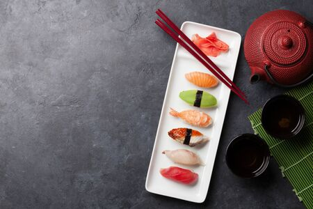 Japanese sushi set. Sashimi, maki rolls and green tea. On plate over stone background with space for your text. Top view flat lay Stock fotó