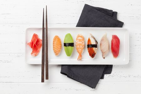 Japanese sushi set. Sashimi, maki rolls. On plate over wooden background. Top view flat lay