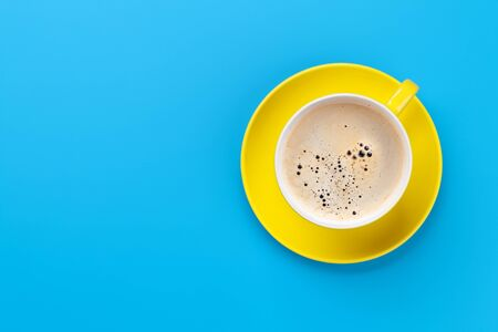 Yellow coffee cup over blue background. Top view flat lay with copy space