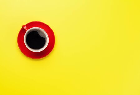 Red coffee cup over yellow background. Top view flat lay with copy space