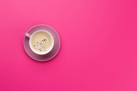 Purple coffee cup over magenta background. Top view flat lay with copy space
