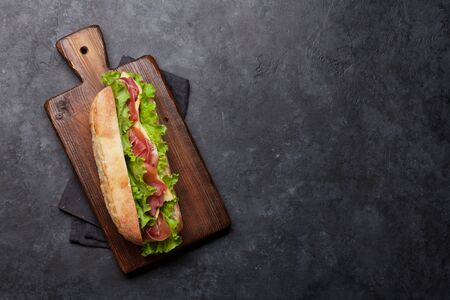 Fresh submarine sandwich with prosciutto ham, cheese and lettuce on dark stone background. Top view with copy space