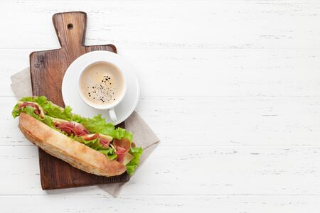 Fresh submarine sandwich with prosciutto ham, cheese and lettuce with coffee cup on wooden background. Top view with copy space for text 写真素材