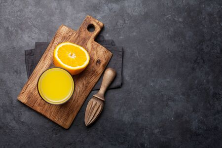 Fresh orange juice and oranges on stone table. Top view with copy space