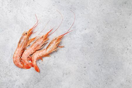 Fresh seafood. Langostino shrimps on a stone background. Top view flat lay. With copy space for your text