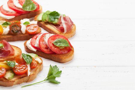 Tapas espagnoles traditionnelles avec tomates, mozzarella, avocat et prosciutto sur fond de bois. Avec espace copie