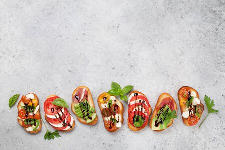 Traditional spanish tapas with tomatoes, mozzarella cheese, avocado and prosciutto on stone background. Flat lay. Top view with copy space Foto de archivo - 127658469