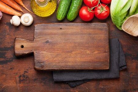 Verschiedene rohe Bio-Gemüse, Kräuter und Gewürze. Frisches vegetarisches Essen im Garten kochen. Draufsicht auf Steintisch mit Schneidebrett für Kopienraum