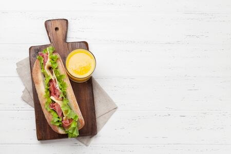 Fresh submarine sandwich with prosciutto ham, cheese and lettuce on wooden background. Top view with copy space for your text
