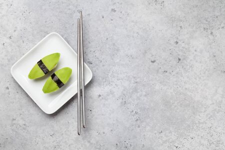Japanese sushi set with avocado. On plate over stone background with space for your text Stock Photo