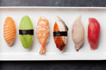 Japanese sushi set. Sashimi, maki rolls. On plate over stone background. Top view flat lay Stock Photo